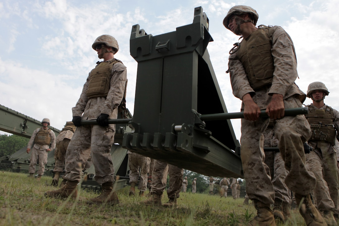 BATTLE CREEK, Mich. – Marines with 6th Engineer Support Battalion use a team-lift technique to move a 300 pound piece of bridge equipment during a training exercise here, June 11. Many of the pieces used to put together a medium girder bridge require more than one Marine to effectively move them.