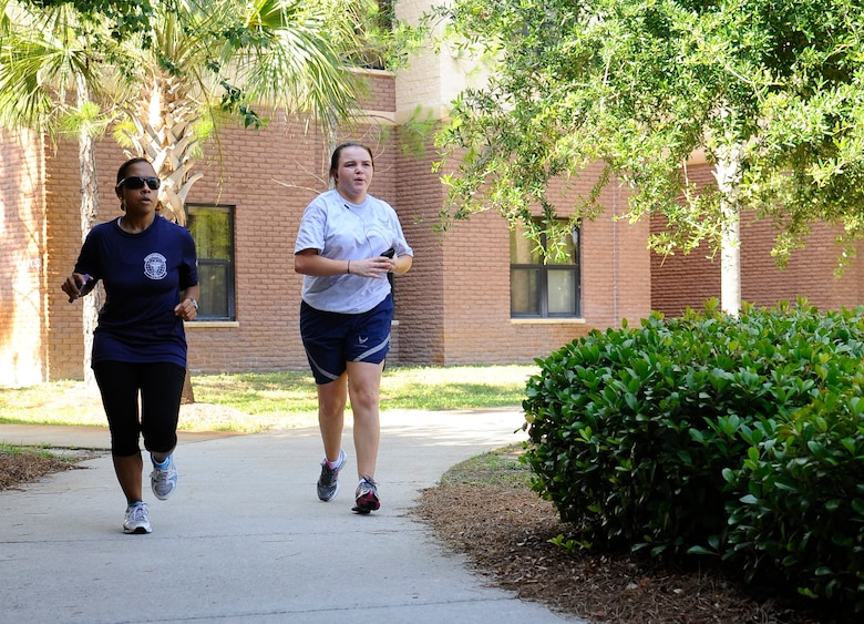 "April Royster, Health and Wellness Center health and fitness specialist, left, helps Senior Airman Chelsea Bolding, 1st Special Operations Dental Squadron dental laboratory technician, keep pace during a mile-and-a-half run outside the Riptide Fitness Center on Hurlburt Field, Fla., June 17, 2013. ""My goal is to train each individual on how to progressively increase their physical training after pregnancy and prepare them for their upcoming fitness assessment test which is due 180 days after delivery,"" Royster said. (U.S. Air Force photo by Airman 1st Class Jeffrey Parkinson)"