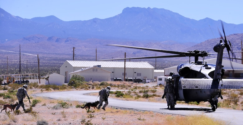 NEVADA TEST AND TRAINING RANGE, Nev. -- Military working dogs and their handlers assigned to the 99th Ground Combat Training Squadron prepare to board and HH-60 Pave Hawk helicopter from the 66th Rescue Squadron outside of Las Vegas June 14, 2013.  The 99th GCTS is the Air Force's largest regional training center and oversees the pre-deployment training for security forces personnel. (U.S. Air Force photo by Staff Sgt. D.H./Released)