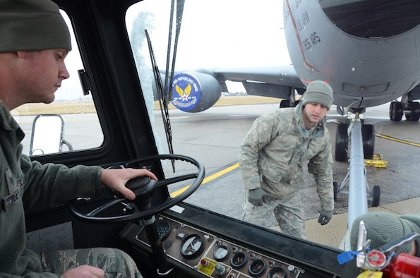 Staff Sgt. Mark Trapp (driver), a crew chief for the 906th Air Refueling Squadron, watches while Staff Sgt. Kenneth Baque (kneeling), a member of the 126th Maintenance Group, and Staff Sgt. David Polcyn, a member of the 906th Air Refueling Squadron, dismount the pivot point from the front of the aircraft tow vehicle while towing a KC-135R Stratotanker on Scott Air Force Base, Ill., March 5, 2013. The pivot point attaches to both the aircraft and the aircraft tow vehicle in order to ease movements. The 906 ARS is an Active  Associate squadron of the 126th Air Refueling Wing, Illinois Air National Guard, and is comprised of Active Duty Air Force members. (National Guard photo by Airman 1st Class Elise Stout)