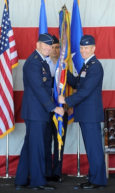 Col. Lance Landrum took the reins of the 388th Fighter Wing during a Change of Command ceremony June 14, 2013, at Hill Air Force Base. From right, Landrum receives the wing guidon from Lt. Gen. Robin Rand, Commander, 12th Air Force, Air Combat Command, and Commander, Air Forces Southern, U.S. Southern Command, who presided over the ceremony while Chief Master Sgt. Daniel McGuire, 388th command chief, looks on. (U.S. Air Force photo by Alex Lloyd/Released).