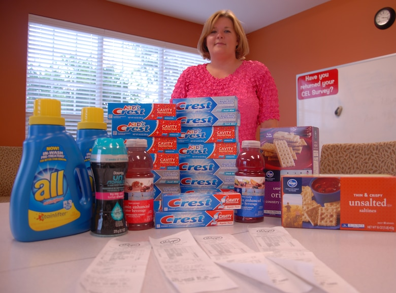 Heather Phillips, a Little Rock Air Force Base Welcome Center leasing agent and couponer, stands behind the groceries she paid only $15 for. Phillips bought 17 tubes of toothpaste for 46 cents at Kroger. Without her coupons her total would have been about $35; she saved more than half the money she spent. (U.S. Air Force photo by Senior Airman Regina Agoha)