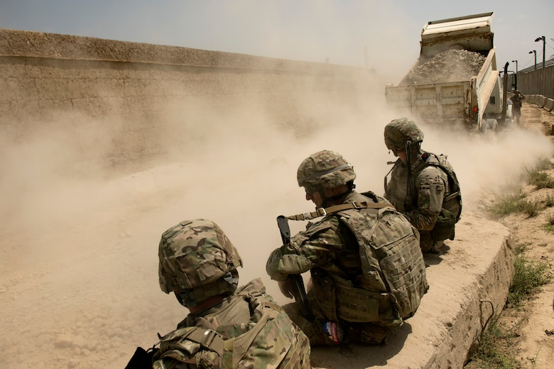 The 455th Expeditionary Security Forces Group airmen watch as a truck dumps gravel on a damaged portion of the road connecting Payan Janqadam with Saka near Bagram Air Field, Afghanistan, June 13, 2013. (USAF Photo/Master Sgt. Ben Bloker)