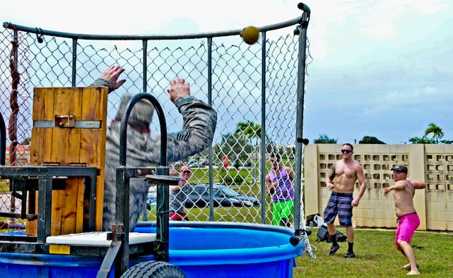 Master Sgt. KC Smith, 36th Contingency Response Group first sergeant, falls into the dunk tank June 14, 2013, on Andersen Air Force Base, Guam, as multiple Airmen hit the target during a Dorm Dweller and Deployer Appreciation day event. The 36th Wing Chapel-funded event was hosted by the 36th Maintenance Group, who organized island-themed performances and games. (U.S. Air Force photo by Airman 1st Class Marianique Santos/Released)