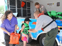 ALBUQUERQUE, N.M., -- Albuquerque District Park Ranger Bob Garcia, Cochiti Lake, shows a young swimmer how a personal flotation device (PFD) should fit properly at the National Get Outdoors Day held at Tingley Beach June 8, 2013. The PFD must be tight enough so it will not come off over a person's shoulders while strapped together.