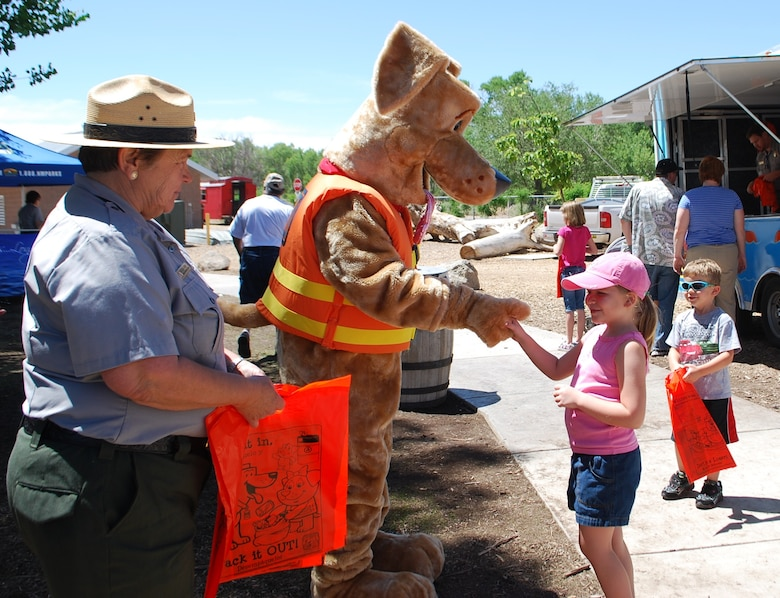 ALBUQUERQUE, N.M., -- Bobber the Water Safety Dog shakes hands with one of the many new friends he made during National Outdoors Day, June 8, 2013.  Kathleen Bennett, outdoor recreation planner with the Albuquerque District, stands by ready to present the child with a bag of water safety goodies.