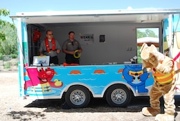 ALBUQUERQUE, N.M., -- Oh no! Bobber the Water Safety Dog misses a Frisbee disc thrown by Ranger John Mueller, Abiquiu Lake. Ranger Bob Garcia, Cochiti Lake, stands by to join in the fun. The rangers are standing in the new Water Safety Trailer.