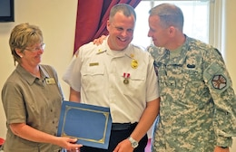 Fort Riley Garrison Commander Col. William Clark, right, and Deputy Garrison Commander Linda Hoeffner, left, present Scott Delay, fire chief, FES, DES, center, with a Superior Civilian Service award at a farewell luncheon June 4 at Building 1020.  Photo by: Julie Fiedler, POST.