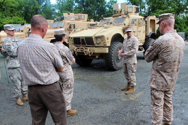 "Lt. Col. Michael Burks (second from right), Joint Light Tactical Vehicle military deputy, stands in the ""gap"" between Mine Resistant Ambush Protected vehicles and a High Mobility Multipurpose Wheeled Vehicle (not shown in photo). He explains to Army and Marine Corps leadership that the JLTV will fill the capability ""gap"" that exists today in both services' light tactical vehicle fleets. This brief took place June 11 during the JLTV demonstration at the Transportation Demonstration Support Area on Marine Corps Base Quantico."