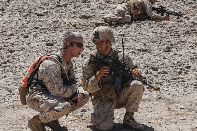 Capt. Nathan Knowles, an explosives ordinance and improvised explosive device coyote with the Tactical Training Exercise Control Group of Marine Corps Air Ground Combat Center Twentynine Palms, Calif., left, provides feedback to an infantry squad leader with 3rd Battalion, 1st Marine Regiment of Marine Corps Base Camp Pendleton, Calif., during a long range raid training exercise in the desert southeast of Marine Corps Air Station Yuma, Ariz., June 3. The coyotes' responsibility is to assess and instruct the Marines training for combat.