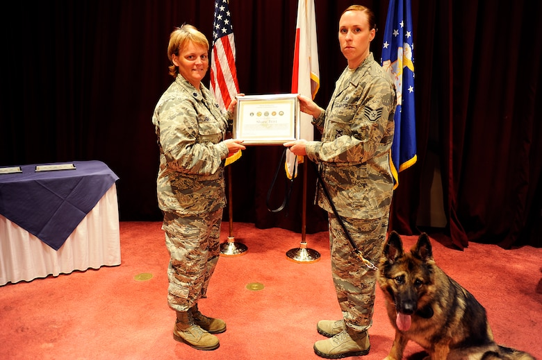 U.S. Air Force Lt. Col. Kathy Jordan, 18th Security Forces Squadron commander, presents Staff Sgt. Codi Carter, 18th SFS military working dog trainer, and her newly adopted MWD, Shara, a MWD Certificate of Meritorious Service during the MWD retirement ceremony on Kadena Air Base, Japan, June 13, 2013. MWD Shara performed nearly 16,000 detector sweeps during her service. Carter is Shara's 10th and final handler. (U.S. Air Force photo by Senior Airman Maeson L. Elleman/Released)