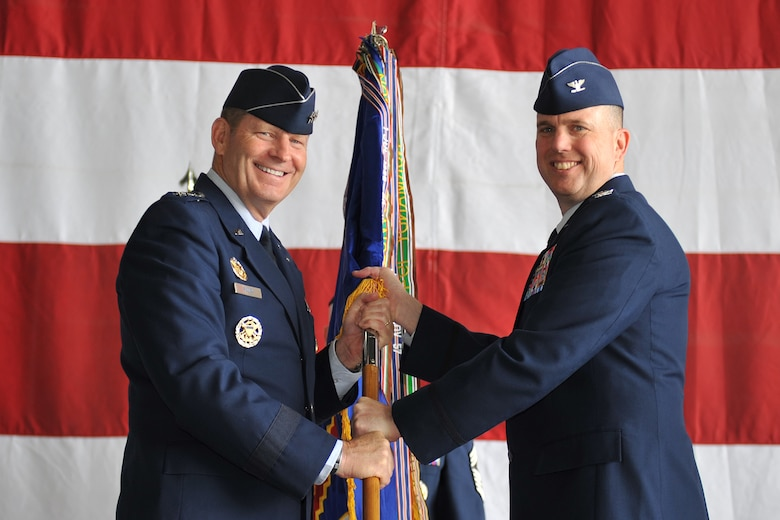 U.S. Air Force Lt. Gen. Robin Rand, 12th Air Force commander, presents the 55th Wing guidon to U.S. Air Force Col. Gregory Guillot, incoming 55th Wing commander, during a formal change of command ceremony in Dock 1 of the Bennie Davis Maintenance Facility June 19 at Offutt Air Force Base, Neb. Hundreds of Airmen, family and distinguished visitors were in attendance for the change of command to welcome the new commander. (U.S. Air Force photo by Jeff W. Gates/Released)