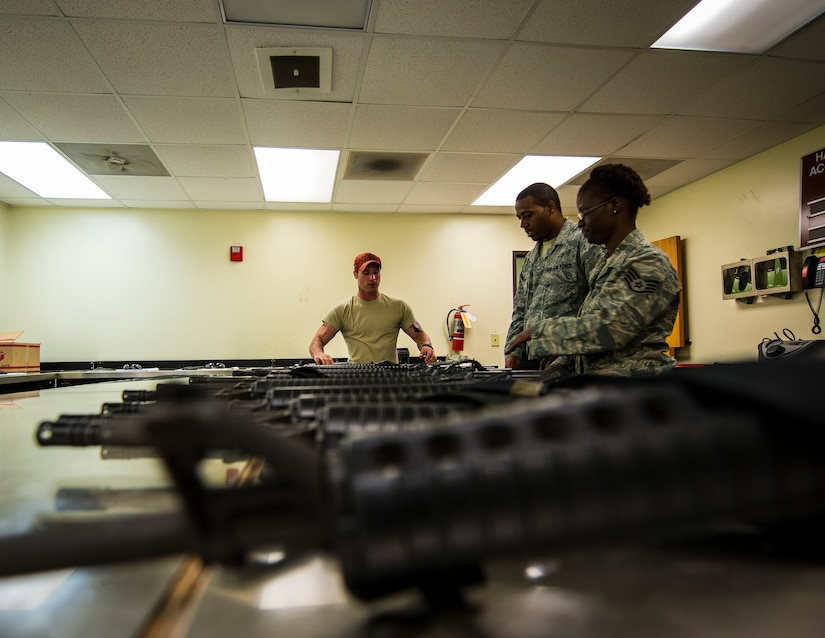 Staff Sgt. Adam Thompson, 628th Security Forces Squadron Combat Arms Training and Maintenance instructor, lines M-16 rifles on an inspection table at CATAM June 13, 2013, at Joint Base Charleston, S.C. The CATAM instructors thoroughly inspect each weapon, looking for cracks, corrosion or general damage to the weapons. (U.S. Air Force photo/ Senior Airman Dennis Sloan)