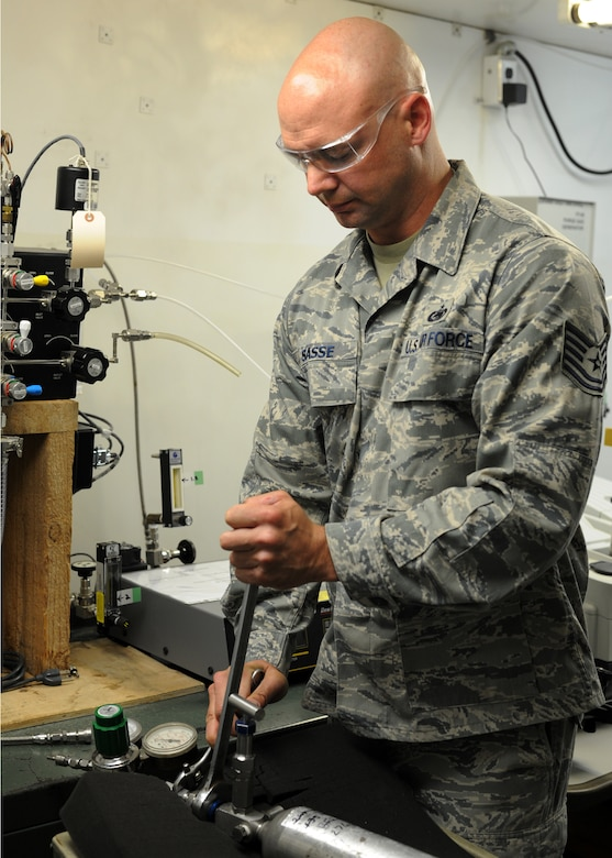 Tech. Sgt. Rocky Sasse tightens a canister to a device used to test gases for purity, odor, moisture and contamination in the 379th Expeditionary Logistics Readiness Squadron Air Force Petroleum Agency Laboratory in Southwest Asia, June 12, 2013. Sasse is the 379th ELRS AFPA NCO in charge of gases deployed from McConnell Air Force Base, Kan. (U.S. Air Force photo/Senior Airman Bahja J. Jones)