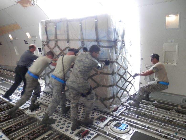 731st Air Mobility Squadron members push a cargo pallet onto a tunner at Kunsan Air Base, Republic of Korea. The 731st AMS ultimately handled 22 cargo aircraft and proved Osan's capability to operate from any location on the Korean peninsula after transitioning to Kunsan for a projected two-month partial runway closure. (Air Force courtesy photo/Master Sgt. David Hardy)