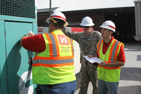 Joseph Rael (right) and Kelly Adams (left) of the Emergency Power team check to ensure a generator is ready for installation during the Combined Response Mission Exercise in Philadelphia. Staff Sgt. James Phillips of the 249th Prime Power Battalion observes activities.