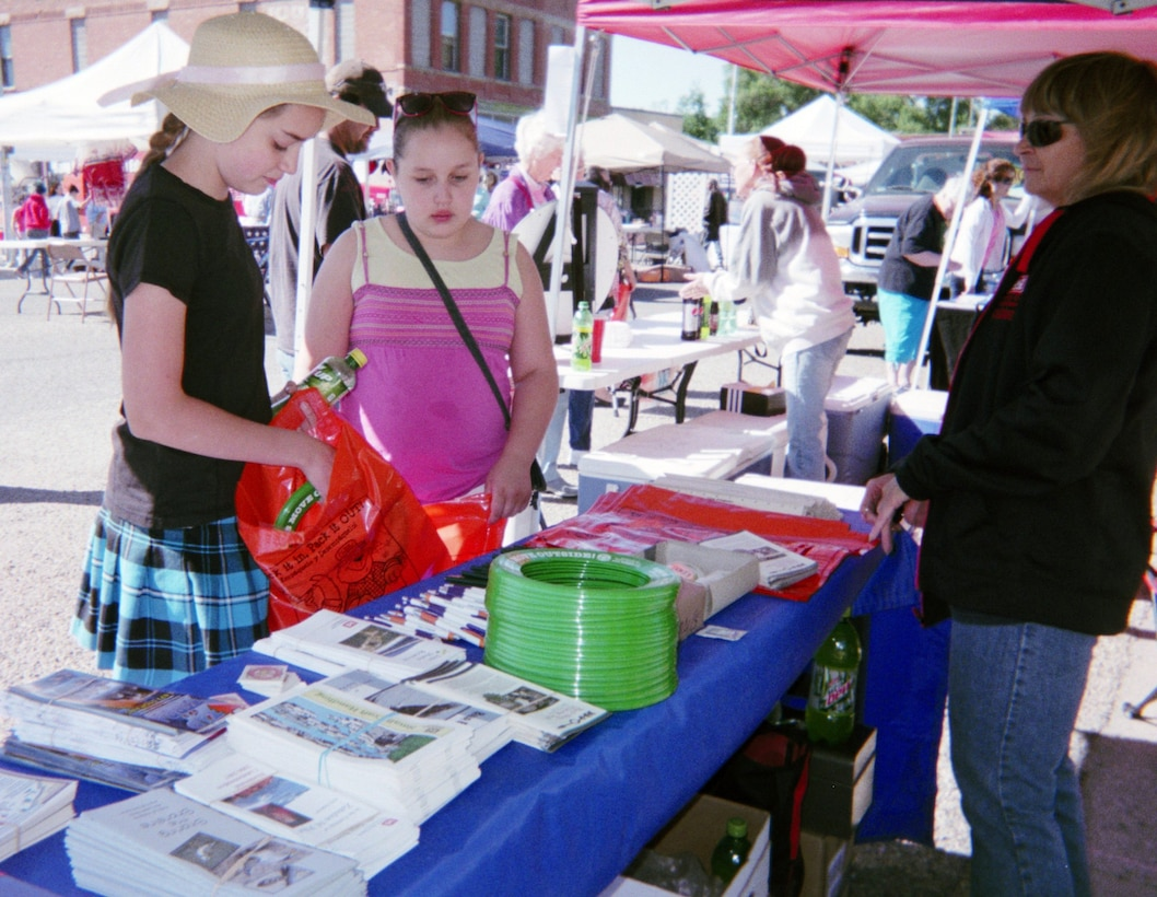 ROCKY FORD, COLO., -- Debby Schibbelhut(R) looks on as two children stop by the Corps' water safety booth at the 9th Annual Cruisin' Into Summer and Keep Kids Safe Fair June 1, 2013. More than 550 children and adults stopped by the booth.