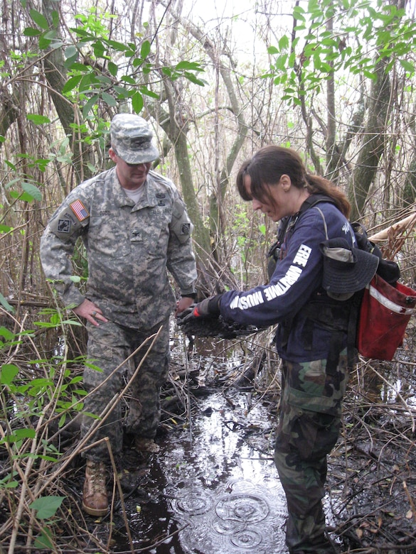 Archaeologist Cynthia Thomas (right), instructs Col. Alan Dodd (left), district commander on archaeological field techniques.