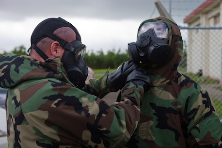 A Marine with Company F., Battalion Landing Team 2nd Battalion, 4th Marines, 31st Marine Expeditionary Unit, tightens the hood of another Marine's Mission Oriented Protective Posture (MOPP) suit during Monitor, Survey and Decontamination Team training at the 31st MEU's Chemical, Biological, Radiological and Nuclear defense warehouse here, June 20. A squad-sized element of Marines from each company and attachment of BLT 2/4 underwent MSD training, designed to give each company a first-responder team for a chemical threat. An MSD team is equipped to identify and isolate an area of suspected hazardous material for a follow-on unit of highly-trained CBRN specialists. The 31st MEU is the only continuously forward-deployed MEU and is the Marine Corps' force in readiness in the Asia-Pacific region.