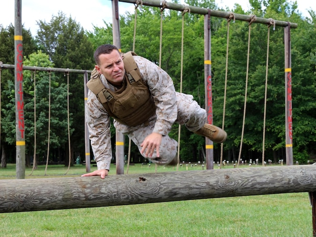 Maj. James Pelland, team lead for Marine Corps Systems Command's Individual Armor Team, jumps over a log to demonstrate the mobility provided by a prototype Modular Scalable Vest, the next generation body armor for the Marine Corps. The MSV will combine attributes from the two most recently fielded protective vests and is being developed by the armor team.