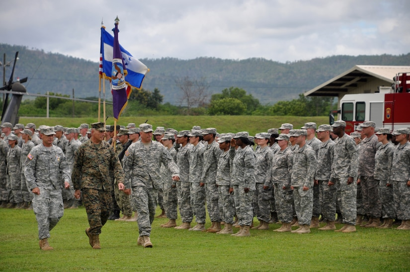 Army Col. Guy A. LeMire(left), Marine Gen. John F. Kelly (center) and Army Col. Thomas D. Boccardi(right) inspect soldiers in formation during the change of command ceremony at Soto Cano Air Base, Honduras, June 20, 2013. The ceremony was held for the out-going  JTF-Bravo  Commander Col. LeMire and the incoming JTF-Bravo Commander Col. Boccardi.