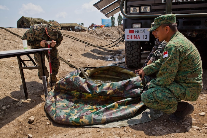 U.S. Marine Sgt. Robert W. Walker, left, helps engineers with China and Singapore set up the Chinese water purification system at a disaster site in Biang, Brunei Darussalam, June 19 as part of the Association of Southeast Asian Nations Humanitarian Assistance/Disaster Relief and Military Medicine Exercise (AHMX). Engineers with China, Singapore and the U.S. demonstrated their water purification capabilities to senior leaders at the disaster site. Walker is a engineer equipment electrical systems technician with 9th Engineer Support Battalion, 3rd Marine Logistics Group, III Marine Expeditionary Force.