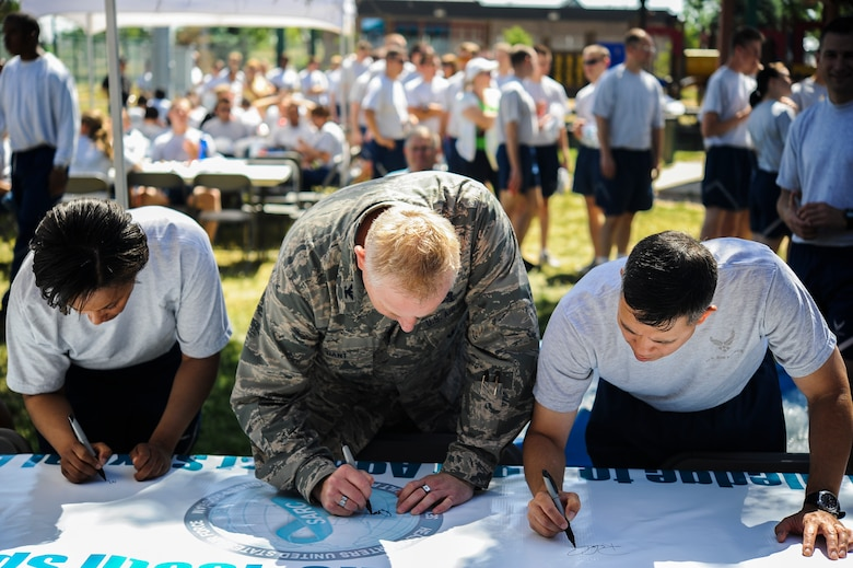 Col. Dan Dant, 460th Space Wing commander, center; Col. Robert Uemura, 460th Mission Support Group commander, right; and Chief Master Sgt. Marilyn Savage, 460th Mission Support Group superintendent, left, sign the Sexual Assault Prevention and Response banner to pledge to fight against sexual assault in the military June 20, 2013, at the fitness center on Buckley Air Force Base, Colo. (U.S. Air Force photo by Staff Sgt. Paul Labbe/Released)