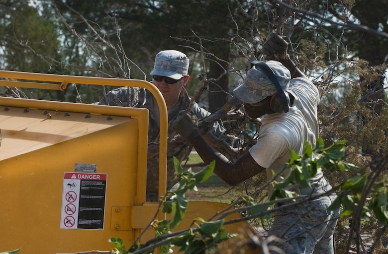U.S. Air Force Staff Sgt. Jerry Ferguson, left, and Airman 1st Class Avery Shaw, right, from the 7th Civil Engineer Squadron (CES), push tree debris through a wood chipper June 18, 2013, at Dyess Air Force Base, Texas. After a storm that hit on June 17, subsided, Airmen from the 7th CES worked early in the morning to restore power to the base and clear roads of debris to ensure Dyess was mission ready. (U.S. Air Force photo by Senior Airman Jonathan Stefanko/Released)