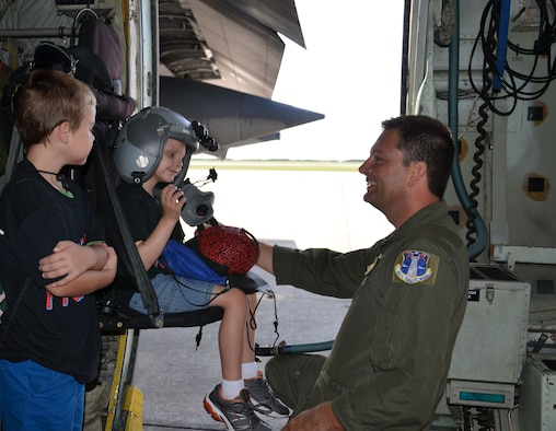 "Senior Master Sgt. Eric Draper, HC-130P/N King reserve loadmaster, helps Trevor Scheerer, 5, with a helmet while Finnian Gerts, 7, watches. The boys and their families visited the 920th Rescue Wing, Cocoa Beach, Fla., to learn about combat search and rescue and meet the rescue professionals. They were treated to a day they would never forget - tours of both rescue aircraft, the King and HH-60G Pave Hawk helicopters, then finished with a ""rescue mission"" hosted by the pararescuemen here."