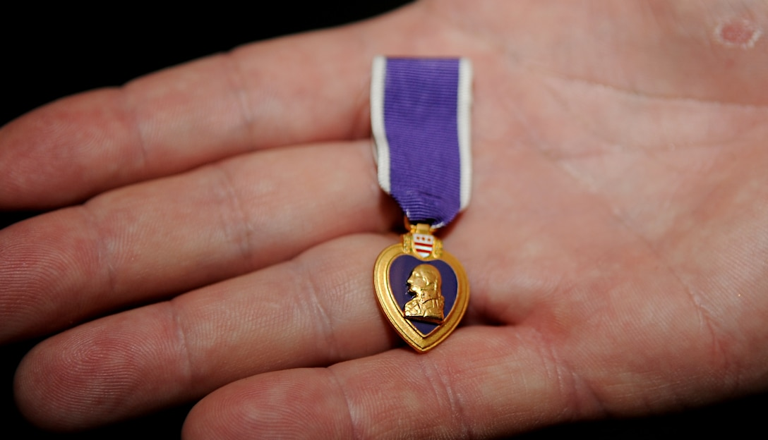 Paul Blais holds his Purple Heart medal in his hand, May 15, 2013. Blais was awarded the medal after he survived the Khobar Tower bombing, June 25, 1996. (U.S. Air Force photo by Staff Sgt. Jarad A. Denton/Released)