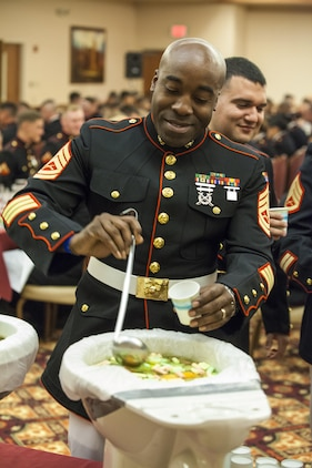 Marines of Marine Air Control Squadron 1 drink of the grog, a mysterious solution of unknown liquids, at the MACS-1 Mess Night on Marine Corps Air Station Yuma, Ariz., at the Sonoran Pueblo, June 7. The Mess Night is a Marine Corps tradition that brings a unit together for an evening of dining and camaraderie.