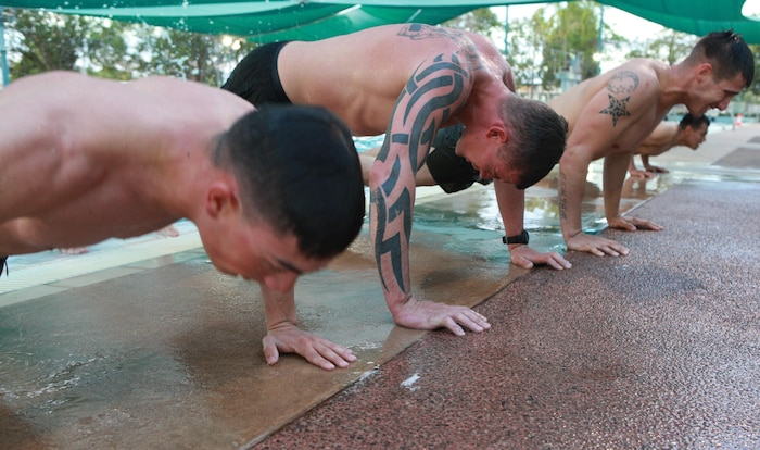Corporals Course students complete pushups after swimming across a pool during a physical training session, here, June 21. The course provides corporals with the education and skills necessary to lead Marines. Two Australian soldiers and a Navy corpsman enrolled in the course to further their Marine Corps knowledge.