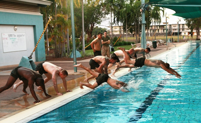 Corporals Course students jump into a pool during a physical training session, here, June 21. The course provides corporals with the education and skills necessary to lead Marines. Two Australian soldiers and a Navy corpsman enrolled in the course to further their Marine Corps knowledge.