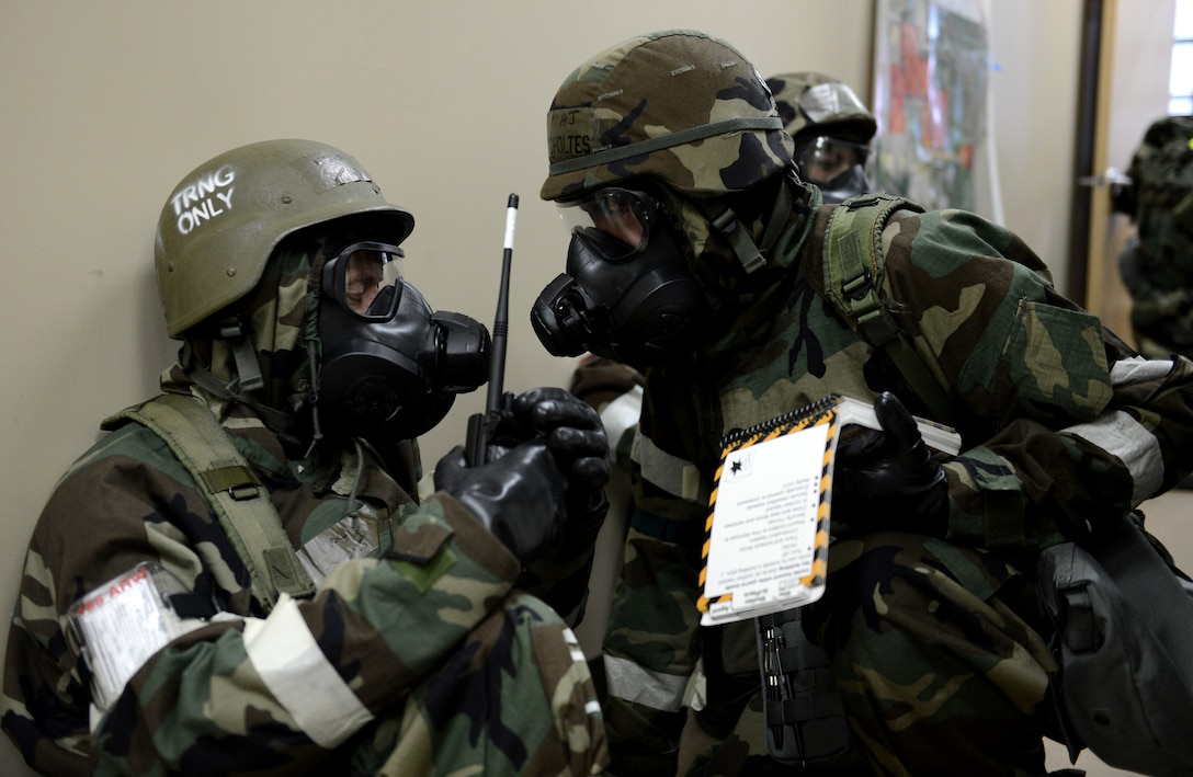 Col. Chris Collins (left), commander of the Nebraska Air National Guard's 155th Air Refueling Wing Operations Group, and Maj. Bryan Scholtes, a wing plans officer, communicate in full chemical suits as they participate in an Ability to Survive and Operate exercise at the Nebraska National Guard air base in Lincoln, Neb., June 11, 2013. Members of the 155th ARW participated in the ATSO to evaluate and improve their capabilities and skills in a wartime scenario. (U.S. Air National Guard photo by Staff Sgt. James Lieth/Released)