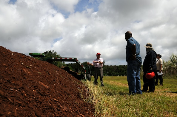 Mohammad Golabi, University of Guam associate professor of soil and environmental sciences, explains how he uses mulch provided by Andersen Air Force Base, Guam, for a composting experiment at the UOG Research Farm in Yigo, Guam, June 19, 2013. The professor, technicians and students collected nearly 250 cubic yards of mulch from Andersen AFB throughout the year for a project that will benefit the local agriculture community. (U.S. Air Force photo by Staff Sgt. Melissa B. White/Released)