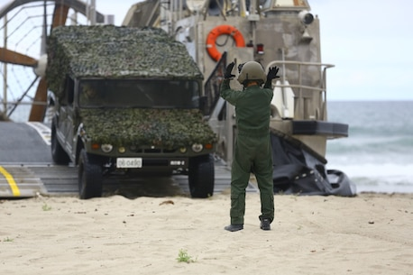 A member of the  Japanese Self Defense Force directs a vehicle during an offload on Red beach here. U.S., Japanese and coalition forces performed a joint exercise with coordinated offloads and beach landing scenarios as part of exercise Dawn Blitz. Dawn Blitz 2013 is a multinational amphibious exercise off the Southern California coast that refocuses Navy and Marine Corps and coalition forces in their ability to conduct complex amphibious operations essential for global crisis response across the range of military operations. (Photo by: U.S. Marine Corps Cpl. Jonathan R. Waldman, Combat Camera, 11TH Marine Expeditionary Unit)