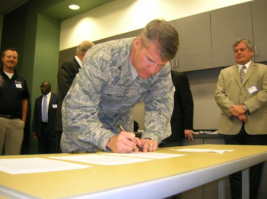 Col. Christopher Hill, Installation commander, signs one of four agreements June 24, 2013, as part of a new community partnership program. The program, called the Air Force Community Partnership Initiative, was created to explore cost-saving opportunities through partnerships and shared services with local communities and the private sector. (U.S. Air Force photo by Roland Leach)