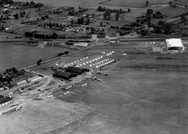 """An aerial view of Camp Lambert at Robertson Field, August 1928.   The training site of the 110th Observation Squadron, Missouri National Guard, Hanger 1 on the top right is under construction.  Towards the center of the photo by the darker colored hangers is an aircraft which some have identified as Lindbergh's """"Spirit of Saint Louis.""""  (131st Bomb Wing file photo/RELEASED)"""