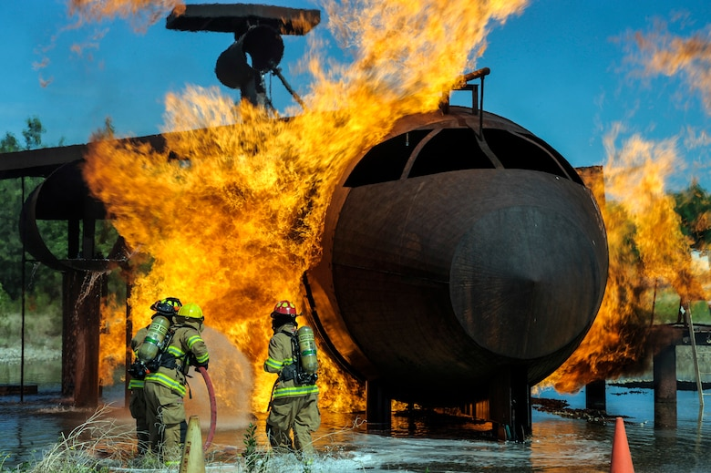 Firefighters with the 354th Civil Engineer Squadron Fire Department attempt to put out a flame on an aircraft fire trainer June 17, 2013, Eielson Air Force Base, Alaska. Fire training prepares firefighters to work as a team in the event that a fire hazard occurs. (U.S. Air Force photo by Senior Airman Zachary Perras/Released)