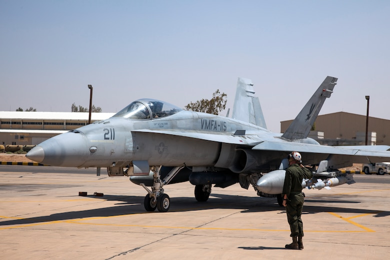 Marine Lance Cpl. Aaron Broering from the VMFA-115 squadron salutes his pilot, Captain Matthew Holcomb as he prepares for takeoff in the F-18 aircraft during the Eager Lion exercise. The Marine Fighter Attack squadron is operating out of a training base in Northern Jordan. Eager Lion is a U.S. Central Command-directed, irregular warfare-themed exercise focusing on missions the United States and its coalition partners might perform in support of global contingency operations. (U.S. Air National Guard photo by Senior Master Sgt. John P. Rohrer)