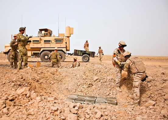 U.S. Air Force and Slovakian explosive ordnance disposal personnel unload a trailer and carefully place ordnance for a controlled detonation near Kandahar Airfield, Afghanistan, June 12, 2013. U.S. Air Force, U.S. Army, Slovakian and Australian EOD personnel participated in a joint mission to dispose of excess military ordnance. (U.S. Air Force photo/Senior Airman Scott Saldukas)
