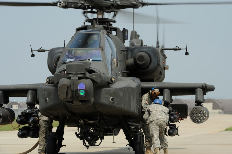 Helicopter crew chiefs, U.S. Army Spcs., Frank Lawson, front, and Pedro Medina, Delta Company, 4th Aerial Reconnaissance Battalion (Attack), 2nd Aviation Regiment, AH-64D Apache Longbow Attack helicopter armament, electrical and avionics systems repairer, Camp Humphreys, Republic of Korea, load an AGM-114F Hellfire Missile onto an AH-64 Apache Longbow helicopter at Kunsan Air Base, ROK, during a live-fire exercise at Jik-Do Island, ROK, June 7, 2013. Pilots fired a total of 87 AGM-114F Hellfire Missiles during their annual training. (U.S. Air Force photo/ Staff Sgt. Tong Duong/ Released)
