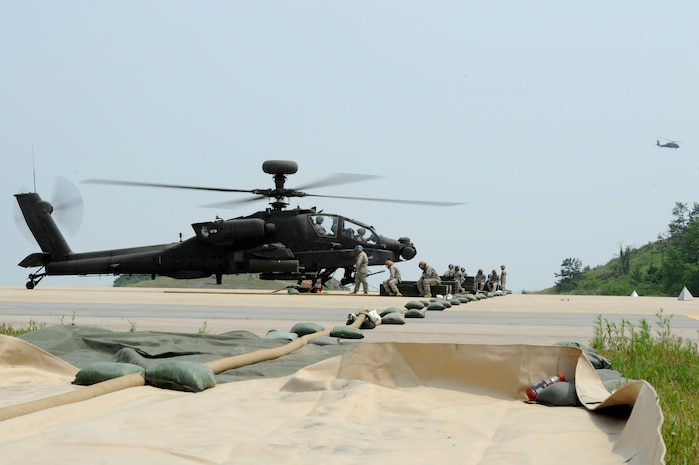 A U.S. Army AH-64 Apache Longbow helicopter prepares to take off from Kunsan Air Base, Republic of Korea, after rearming and topping off on fuel, June 7, 2013. The Army conducts annual live-fire training at Jik-Do Island, which is an instrumented range facility on two islands off the western coast of Korea, near Kunsan. (U.S. Air Force photo/ Staff Sgt. Tong Duong/ Released)
