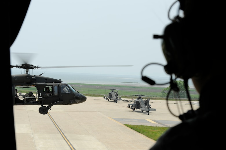 A U.S. Army UH-60 Black Hawk helicopter prepares to land on Kunsan Air Base, Republic of Korea, as a pair of AH-64 Apache Longbow helicopters wait to be serviced after a live-fire exercise at Jik-Do Island, ROK, near Kunsan, June 7, 2013. Twelve helicopters assigned to the 4th Aerial Reconnaissance Battalion (Attack), 2nd Aviation Regiment, from Camp Humphreys, ROK, staged out of Kunsan, during their week-long live fire training. (U.S. Air Force photo/ Staff Sgt. Tong Duong/ Released)