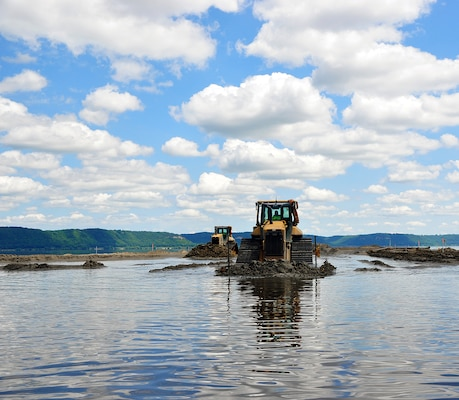 Walking on water? Not quite. One aspect of the Corps of Engineers not often seen is our Environmental Management Program. Here, a bulldozer moves dredge material to create islands in the Mississippi River. Specifically, the Capoli Slough Habitat Restoration project is located in Pool 9, downstream of Lansing, Iowa, on the Wisconsin side of the river, where erosion from wave action and main channel flows is reducing the size of wetland areas. This has resulted in the loss of aquatic vegetation and the shallow habitats important for the survival of many species of fish and wildlife. The project is broken down into two stages, and consists of creating 12 islands, improving backwater habitat, bank stabilization and other measures to improve the habitability. Once completed, the project will be turned over to the U.S. Fish and Wildlife service for day-to-day management.