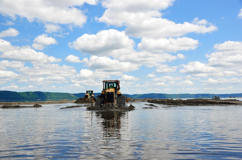 Bulldozers move dredge material to create islands in the Mississippi River as part of the Capoli Slough Habitat Rehabilitation and Enhancement Project.