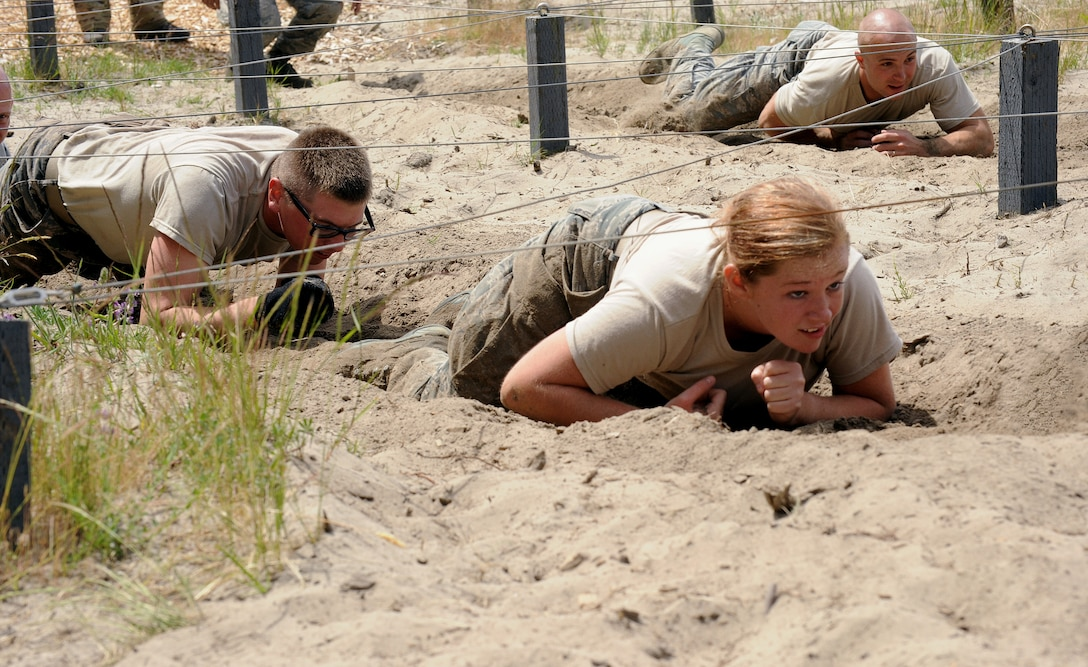Air National Guard Senior Airman Brittani Schammen, 116th surveillance technician, makes her way under an obstacle during the 'Monster Mash' training exercise, June 22, 2013 at Camp Rilea, Ore. The training was held over a five-day period in which the Combat Operations Group (COG) made up of four individual Oregon Air Guard units; 125th STS, 116th ACS, 270th ATCS and the 123rd WF. The focus of the training was to build unit morale, establish new professional networks and enhance military development. (Air National Guard photo by Tech. Sgt. John Hughel, 142nd Fighter Wing Public Affairs)