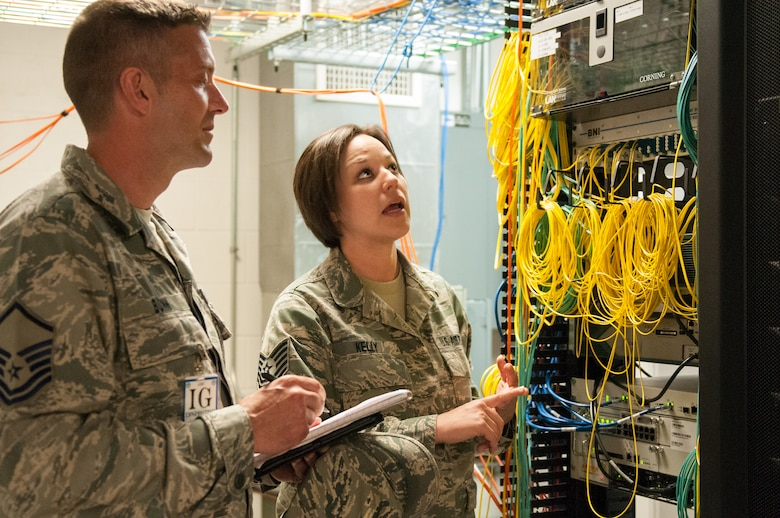 Tech. Sgt. Kristin Kelly, cyber transport technician for the Kentucky Air National Guard's 123rd Communications Flight, examines the 123rd Airlift Wing's base network infrastructure with Master Sgt. Kyle Bunn, an inspector from Air Mobility Command, as part of a Consolidated Unit Inspection at the Louisville, Ky., wing May 19, 2013. The unit underwent the multi-disciplinary inspection between May 15 and 22. (U.S. Air National Guard photo by Senior Airman Vicky Spesard)