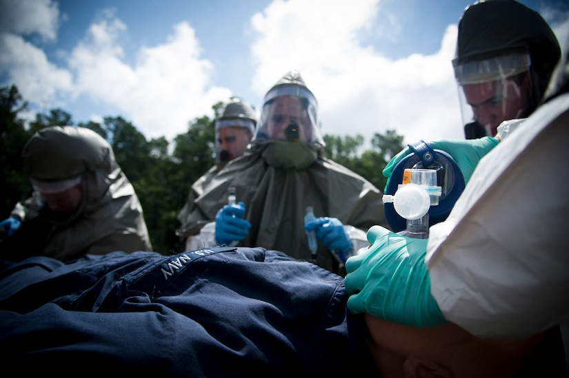 """Sailors from the Navy Health Clinic Charleston simulate preparing a patient for the  decontamination tent during the First Receivers Operations Training course June 21, 2013, at Joint Base Charleston - Weapons Station, S.C. The NHCC team participated in the FROT course to educate their Sailors on life saving skills consisting of triage, initiate field treatment, decontaminate and save victims from Chemical, Biological, Radiological/Nuclear, or Hazardous Material. The 16-hour course consisted of one, eight-hour day of class lecture and a second eight-hour day of """"hands-on"""" teamwork training to include a final """"timed"""" exercise. (U.S. Air Force photo/Staff Sgt. Rasheen Douglas)"""