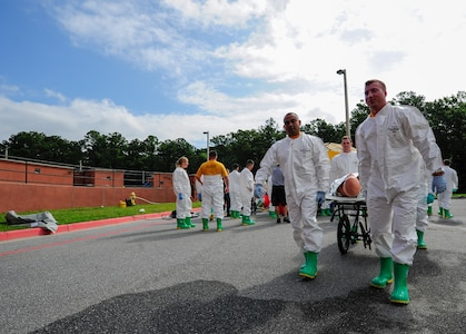 """Sailors from the Navy Health Clinic Charleston simulate carrying a patient to be examined after going through the decontamination tent during the First Receivers Operation Training course June 21, 2013, at Joint Base Charleston - Weapons Station, S.C. The NHCC team participated in the FROT course to educate their Sailors on life-saving skills consisting of triage, initiate field treatment, decontaminate and save victims from Chemical, Biological, Radiological/Nuclear, or Hazardous Material. The 16-hour course consisted of one, eight-hour day of class lecture and a second eight-hour day of """"hands-on"""" teamwork training to include a final """"timed"""" exercise. (U.S. Air Force photo/Staff Sgt. Rasheen Douglas)"""
